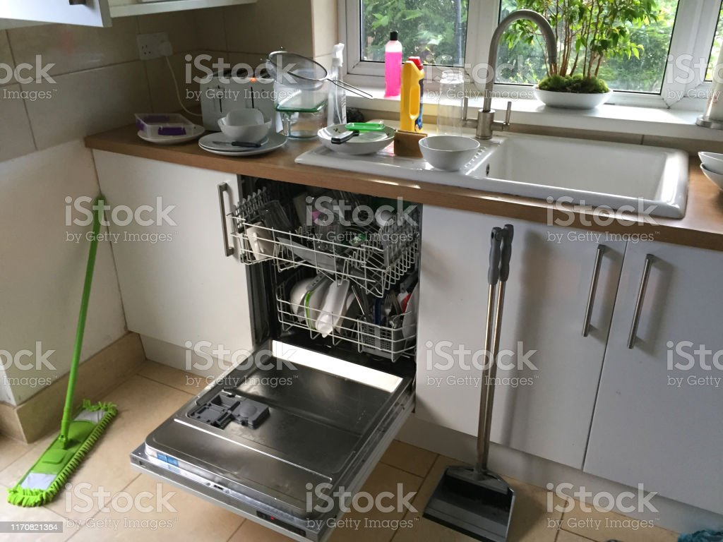Stock photo of dirty messy kitchen with loaded dishwasher open...