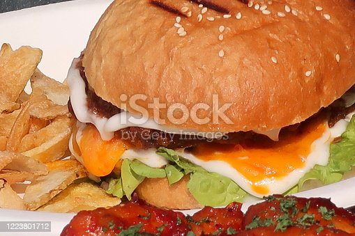 Stock photo showing a take away burger with lettuce leaves and melted cheese on a disposable cardboard plate with a side of crisps. The bun has been toasted and is covered with sesame seeds.
