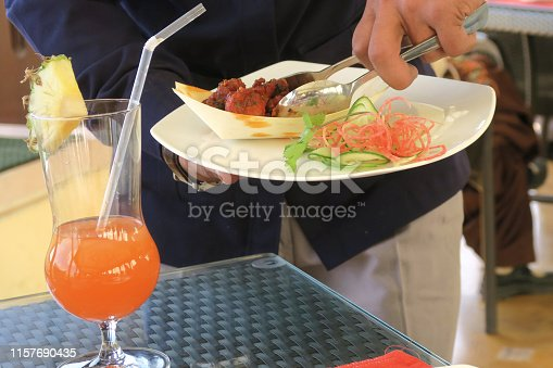 Stock photo of Indian restaurant meal with food being served by waiter using fork and spoon, spicy deep-fried chicken pakoras recipe, dining out with non-veg meat dish on table, served with Indian salad, pineapple orange cocktail drink, Delhi, India
