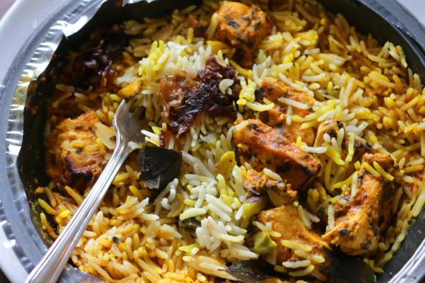 Bild des Essens Supermarkt Takeaway indische Lebensmittel von Huhn Biryani Safran Pilau Reis in Kunststoff-Behälter in der Küche Mikrowelle Fastfood Mittagessen Abendessen gekocht, asiatische Indien aromatische Stücke Huhn, karamellisierte gebratene Zwi – Foto