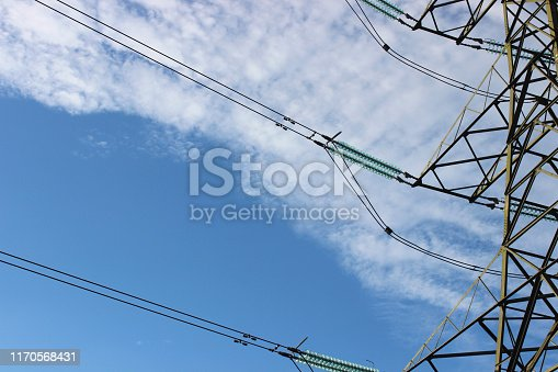 Photo showing a tall high-voltage transmission tower, which is known in the UK and much of Europe as an electricity pylon.  The photo shows a section of the tower, with wires, conductors and insulator strings.  This part of the structure is close to the top (peak) and known as the 'cage', with the 'crossarms' being visible.