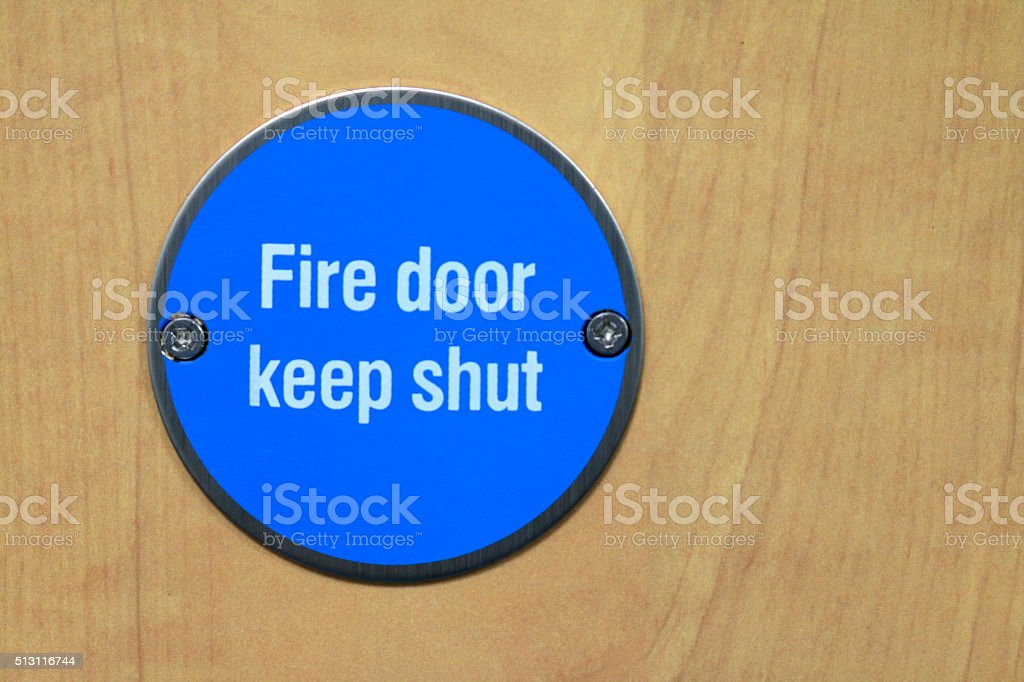 Image of emergency fireproof door with blue-circular advisory sign on stock photo