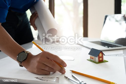istock Image of engineer drawing a blue print design building or house, An engineer workplace with blueprints, pencil, protractor and safety helmet, Industry concept 1089216422