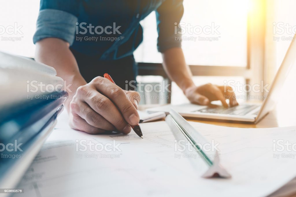 Image of engineer drawing a blue print design building or house, An engineer workplace with blueprints, pencil, protractor and safety helmet, Industry concept stock photo