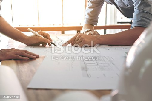 821915804 istock photo Image of engineer or architectural project, Close up of Architects engineer's hands drawing plan on BluePrint and discussing to partner with Engineering tools on workplace, Construction concept 905274438