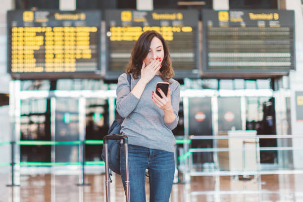 Image of excited, shocked young beautiful woman, standing in airport with smartphone in her hands - missed or cancelled flight concept - flight information board in background Picture of woman in airport watching smartphone jet lag stock pictures, royalty-free photos & images