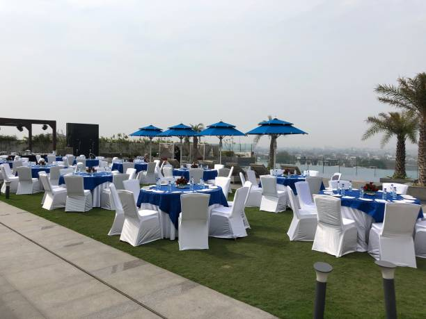 Image of exotic rooftop garden and infinity swimming pool with luxury patio tables and chairs covered in white fabric for lunchtime wedding banquet on green lawn grass, blue parasol umbrella photo stock photo