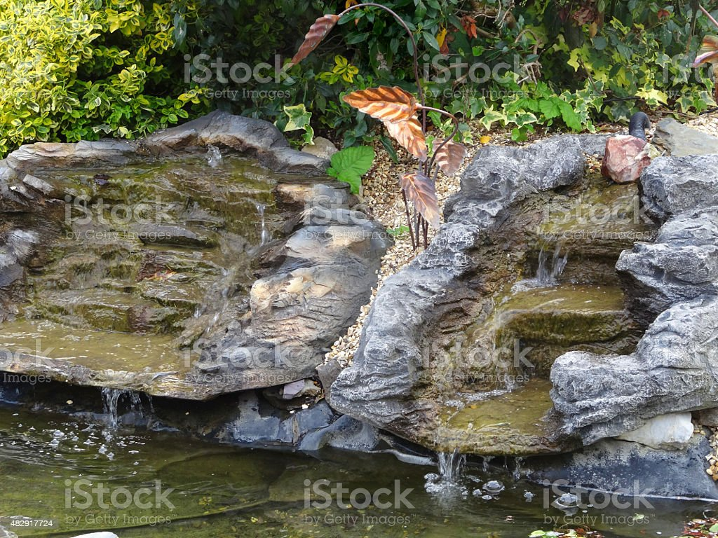Image of fake plastic waterfalls with water cascading into pond stock photo