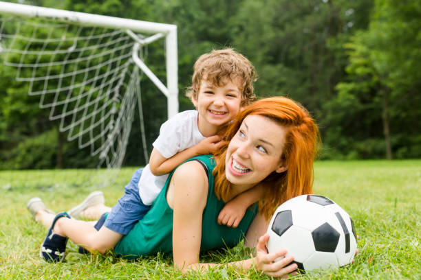 Image of family, mother and son playing ball in the park stock photo