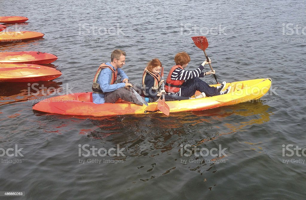 Photo showing a young family on a brightly coloured kayak in a calm...