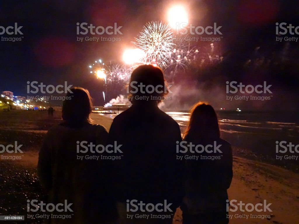 Image of family silhouettes watching seaside fireworks display on beach stock photo