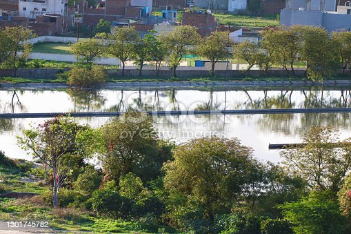 Stock photo of farming field and clean public sewage treatment plant in New Delhi suburbs, India, water being treated and purified for environment by filtration sewerage system, blue sky and trees making Indian sewage plant photo appear like lake wildlife, blue sky copy space
