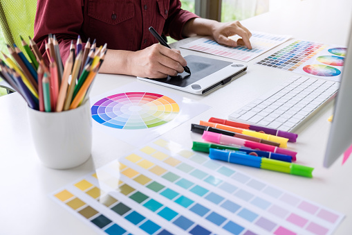 istock Image of female creative graphic designer working on color selection and drawing on graphics tablet at workplace 1057613484