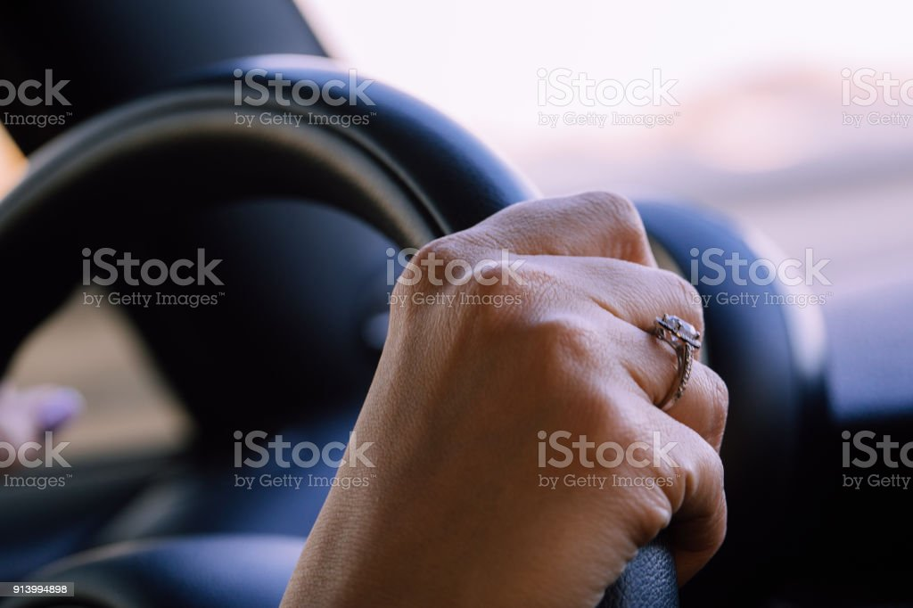 Image of female hands on a steering wheel, steadily driving down a road. stock photo