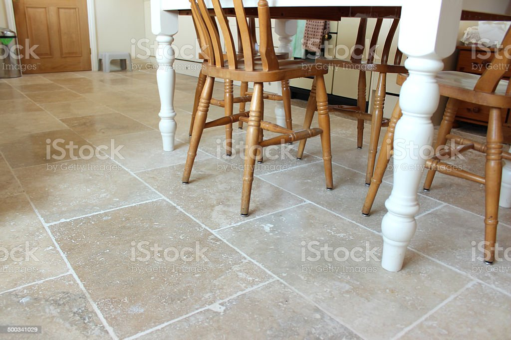 Image of filled travertine tile floor, kitchen table and chairs stock photo