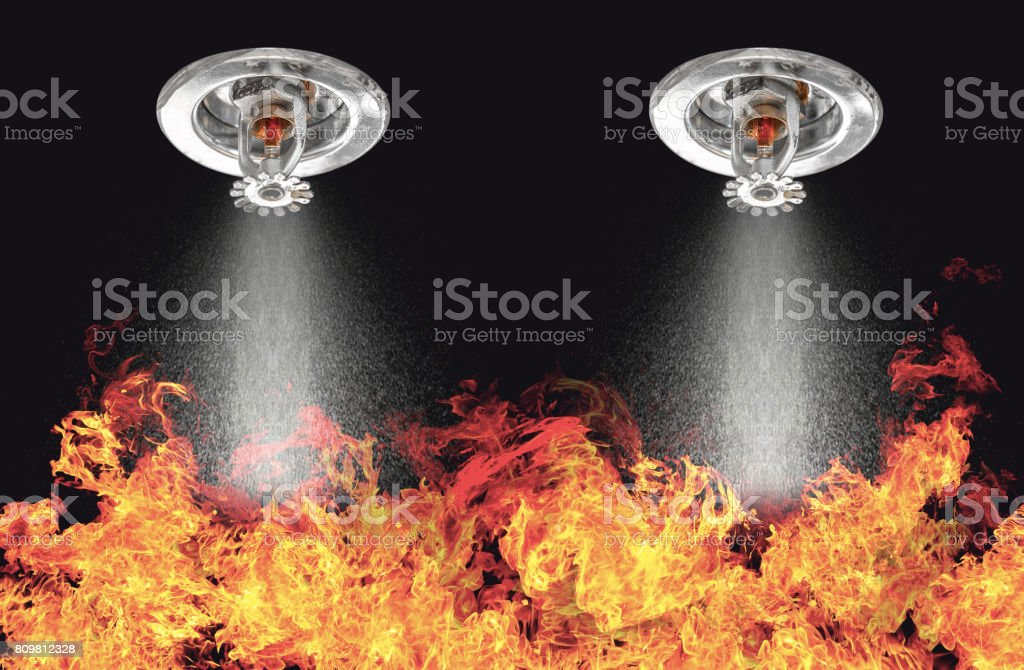 Image of Fire Sprinklers Spraying with fire background. Fire sprinklers are part of an overall safety protocol for fire and life safety. stock photo