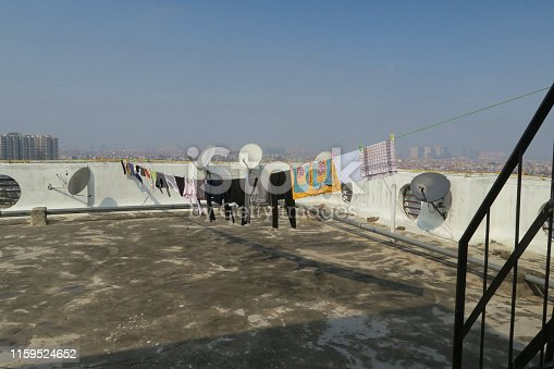Stock photo of flat rooftop washing line drying clothes of bedsheets / sheets, towels and shirts, blowing in breeze to dry on top of Indian apartment block in New Delhi, North India, hazy pollution grey blue sky with distant city views and satellite dishes