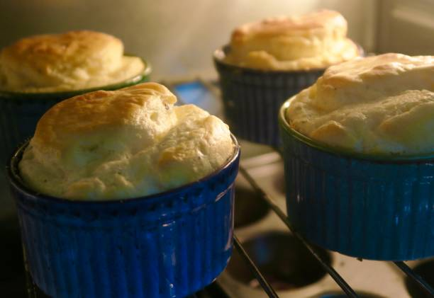 Image of four homemade cheese souffles made with whisked egg whites and herbs, rising in hot oven for dinner party, delicious golden brown cheese souffle starter appetiser cooking in round blue China ramekin dishes, home baking photo on oven grill shelf stock photo