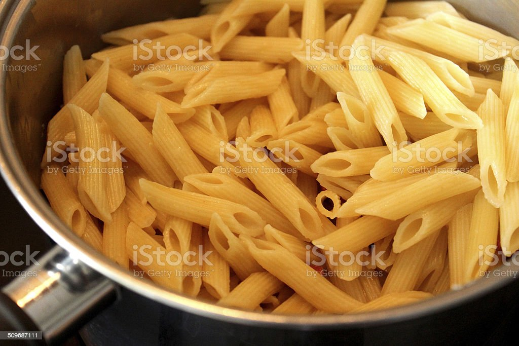 Image of freshly cooked penne pasta in saucepan, awaiting sauce stock photo