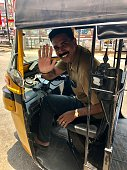 Stock photo showing a friendly, smiling Indian auto rickshaw driver waving from the cab of his black and yellow, three-wheeled vehicle in Kerala, South India.