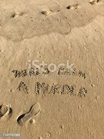 Stock photo of words written on beach sand saying There's Been A Murder, drawn with a stick by the sea, with seaside footprints by the sea.