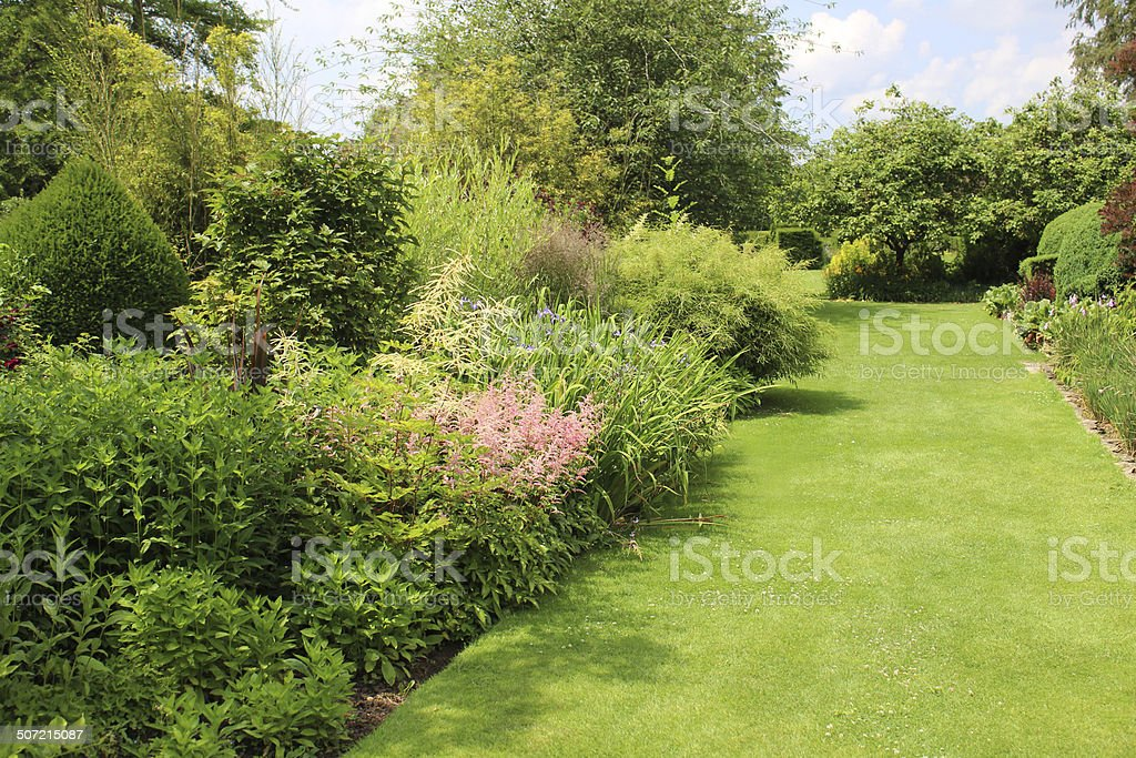 Image of garden lawn pathway with herbaceous border flowers, astilbes stock photo