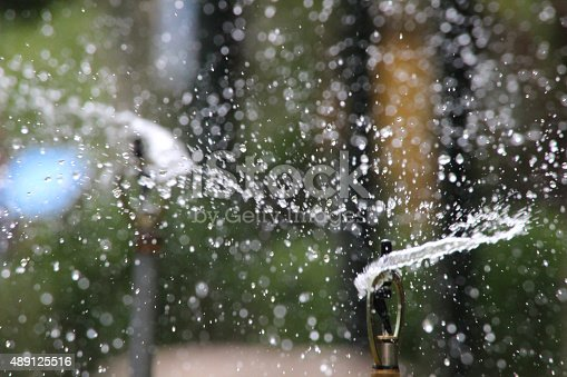 istock Image of garden sprinkler watering grass / flowers, irrigation with water-droplets 489125516
