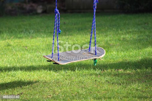 Photo showing a garden swing that has been made from an old skateboard, as part of a recycling project at school.  The upcycled skateboard swing has been tied to the branch of an apple tree with blue rope, suspending it above the lawn.