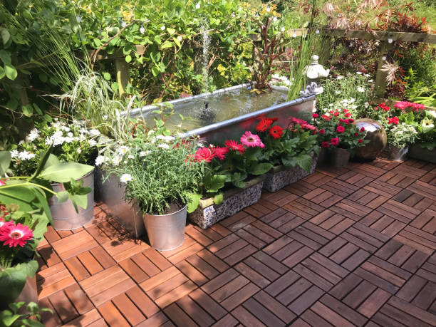 Image of garden treehouse terrace platform balcony in summer with zinc metal trough pond water feature with solar fountain pump, goldfish fish, marginal plants, red miniature roses, pink gerbera flowers, teak decking tiles, solar powered lights, lighting stock photo
