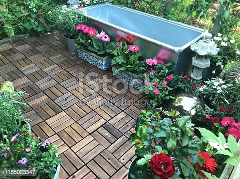 Stock photo of garden treehouse terrace platform balcony in summer with zinc metal trough pond water feature with solar fountain pump, goldfish fish, marginal plants, red miniature roses, pink gerbera flowers, teak decking tiles, solar powered lights, lighting