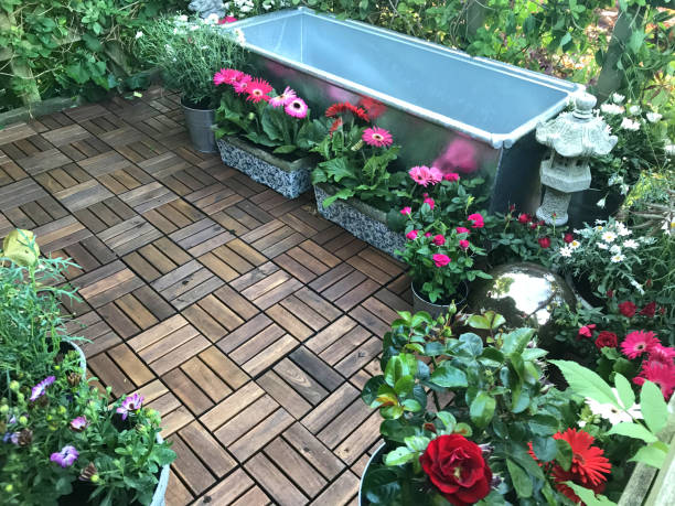 Image of garden treehouse terrace platform balcony in summer with zinc metal raised pond water feature of galvanised cattle trough ready for water, plants, fountain, red miniature roses, pink gerbera flowers, wooden decking tiles, solar lights lighting stock photo