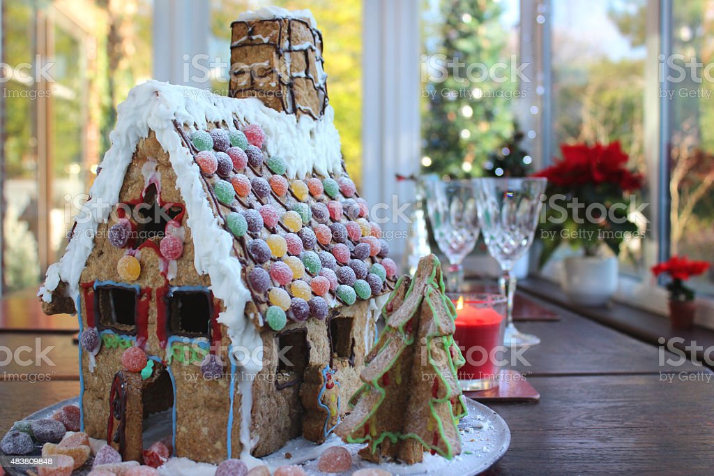 Image of gingerbread house on wooden table with sweets, poinsettias stock photo
