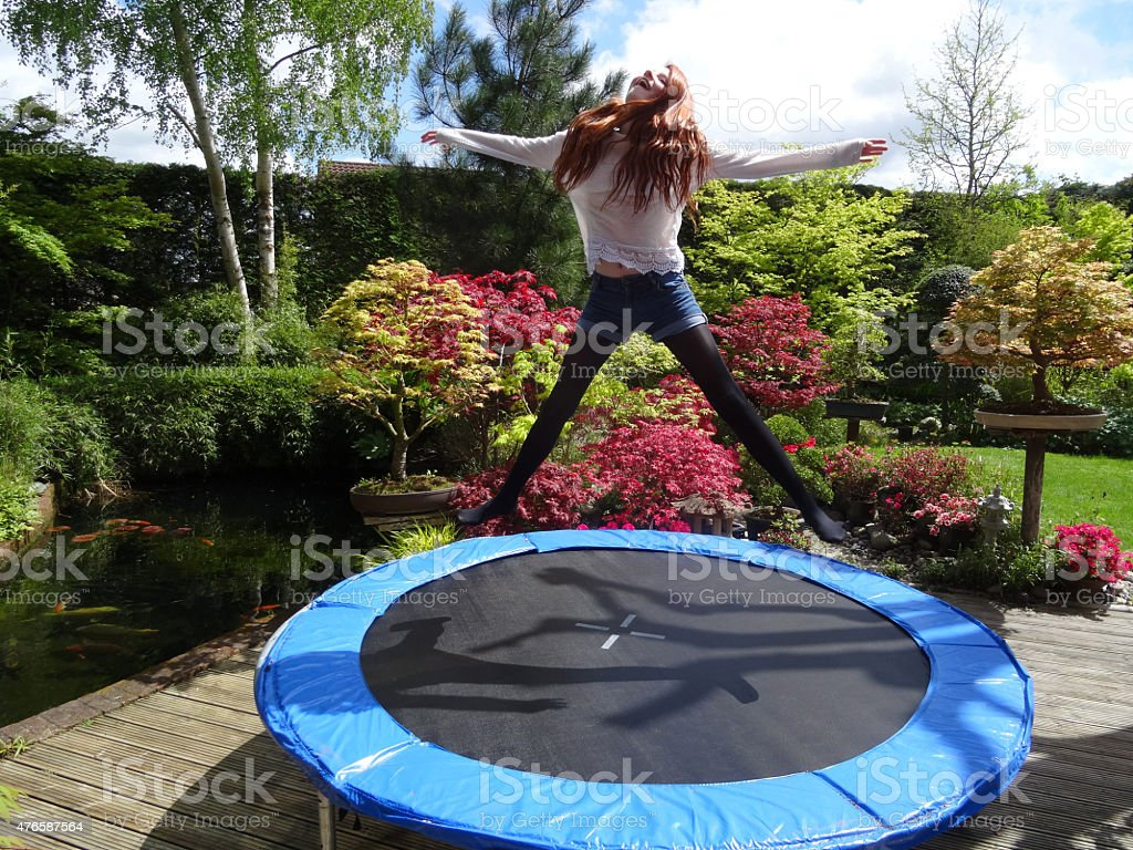 Image Of Girl Bouncing On Garden Trampoline Without Safety Net Royalty Free  Stock Photo
