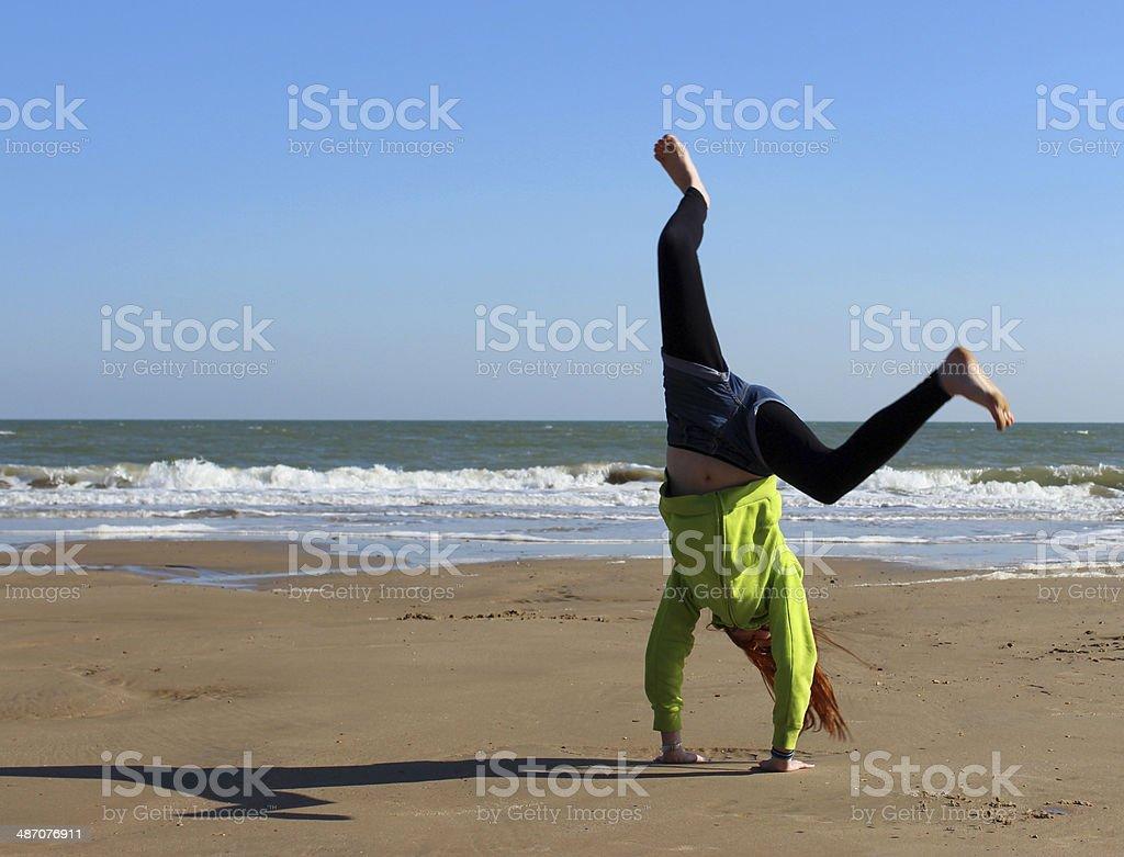 Image of girl doing cartwheel / handstand on Bournemouth beach stock photo