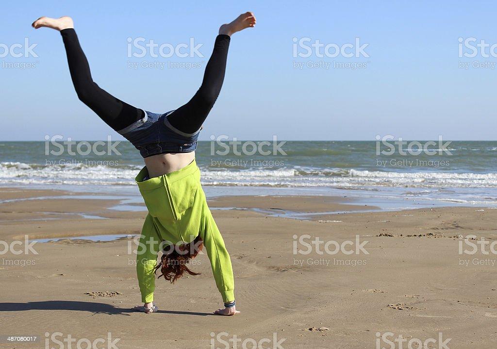Image of girl doing handstand / cartwheel on sandy beach stock photo
