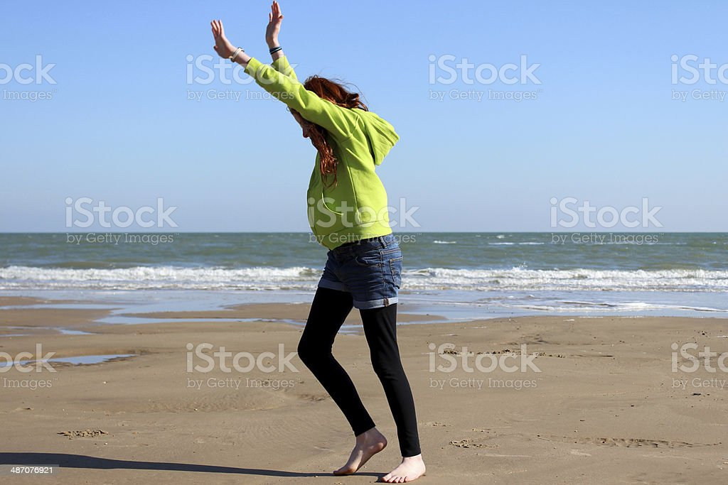 Image of girl exercising on beach, about to do cartwheel stock photo