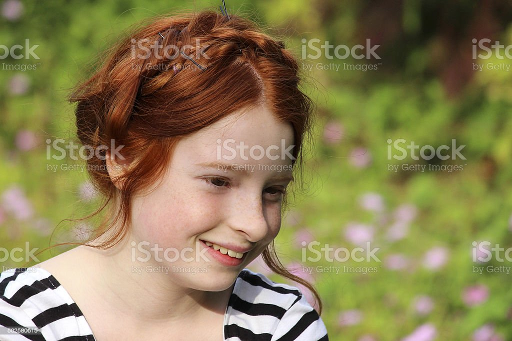Image of girl in garden, smiling with milkmaid braid hairstyle stock photo