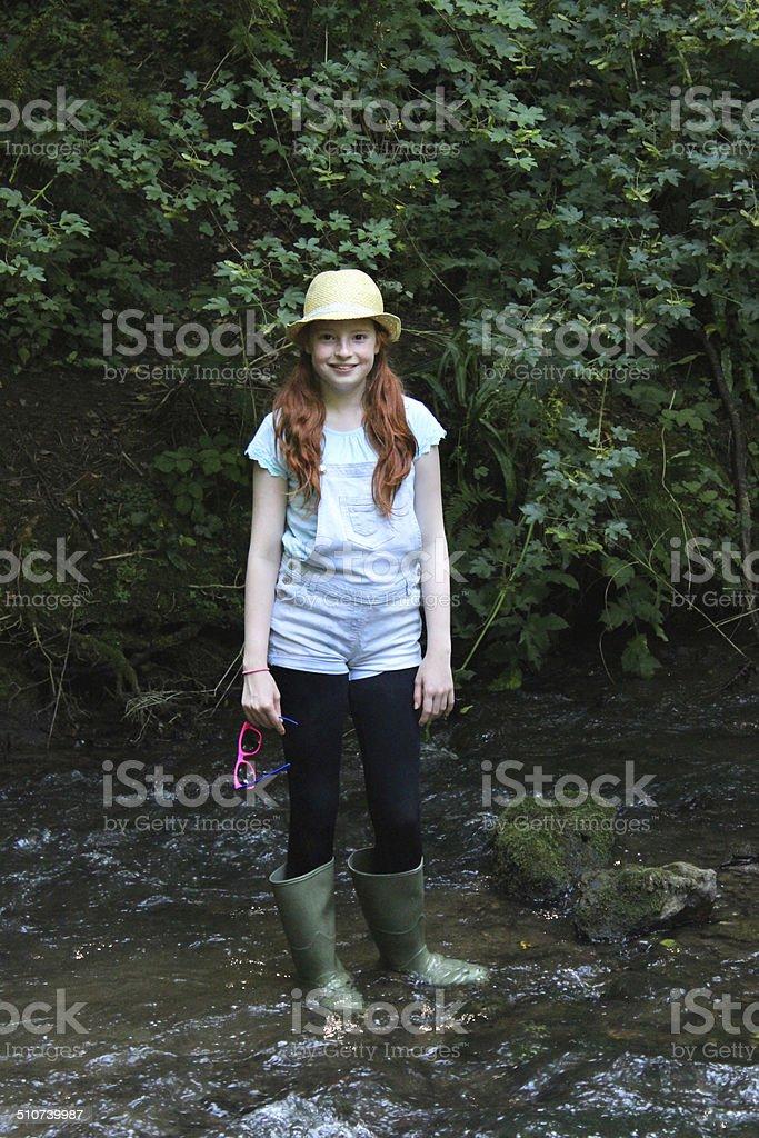 Image of girl playing, paddling, splashing, wading in river, woodland stock photo