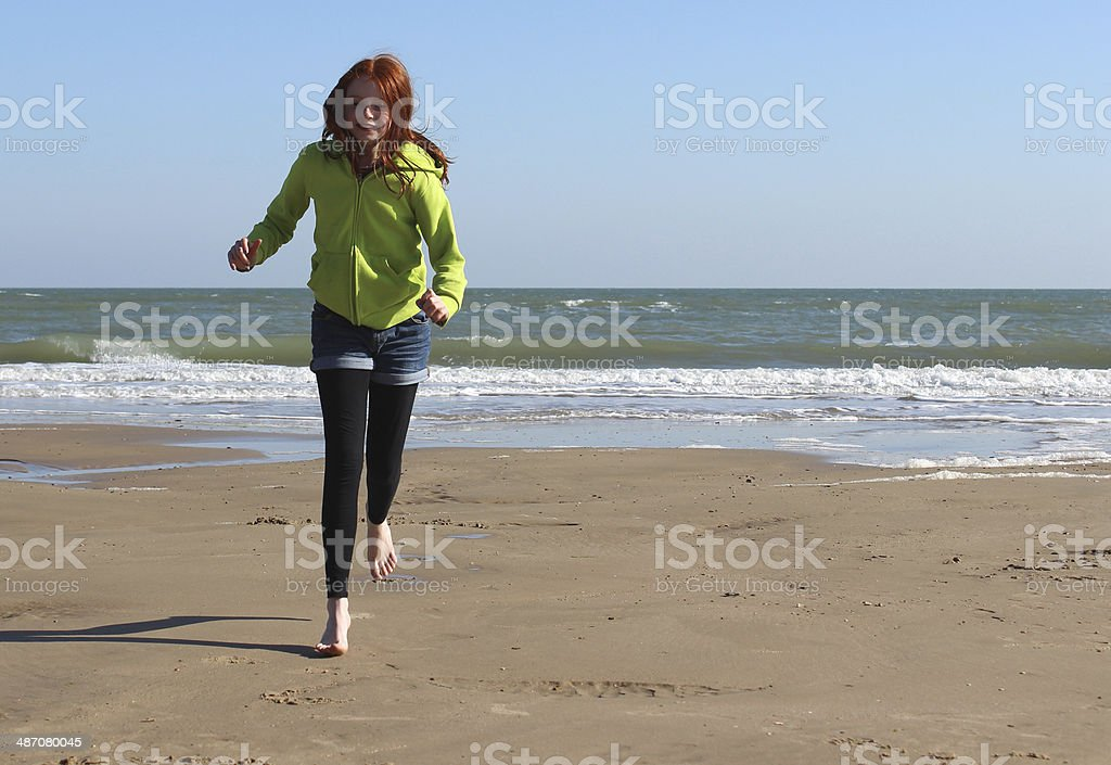 Image of girl running along beach with sea in background royalty-free stock photo