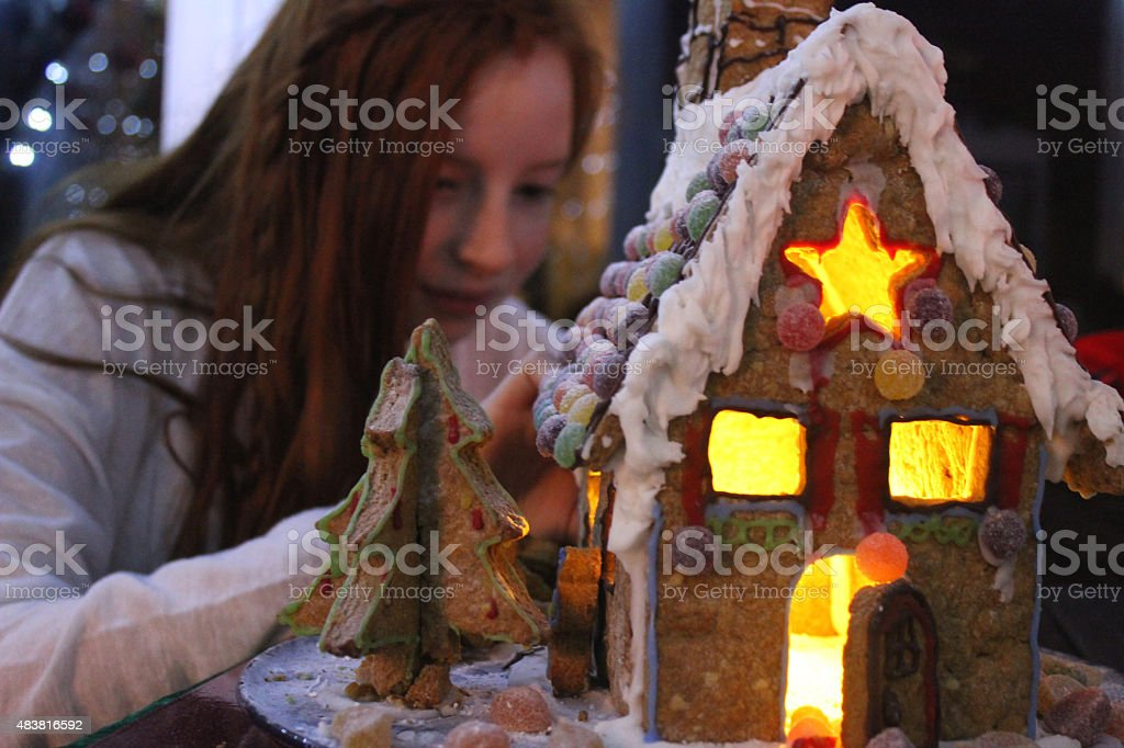 Image of girl sticking sweets on illuminated biscuit gingerbread house stock photo
