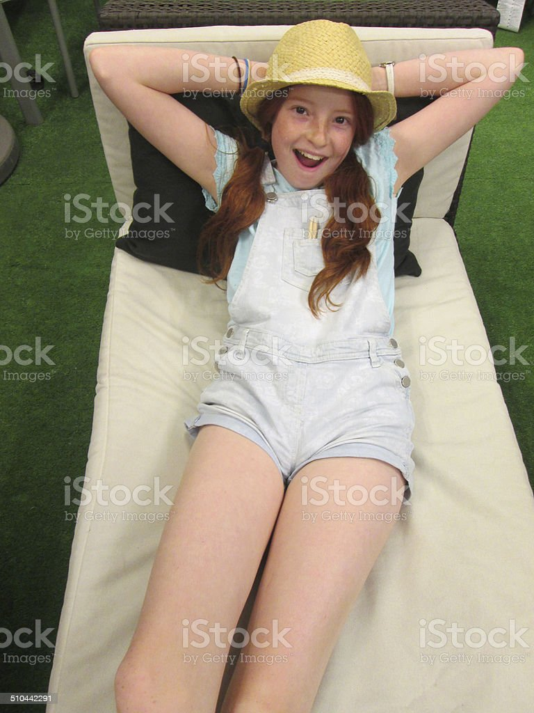 Image of girl sunbathing on wooden garden sunlounger with cushions stock photo