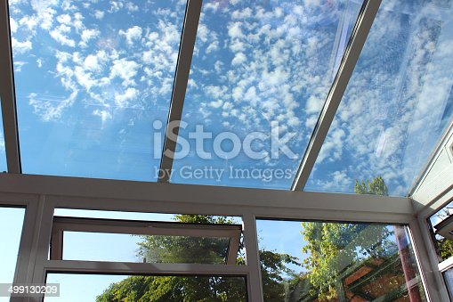 Photo showing a glass conservatory roof with panels of self-cleaning glass.  This glass is slightly tinted and has special properties, helping to reflect the outside heat in the summer and retain the interior heat in the winter.