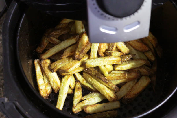 Image of golden brown, fresh crunchy French fries / chunky chips cooked in air fryer, healthier alternative to snack cooking stock photo