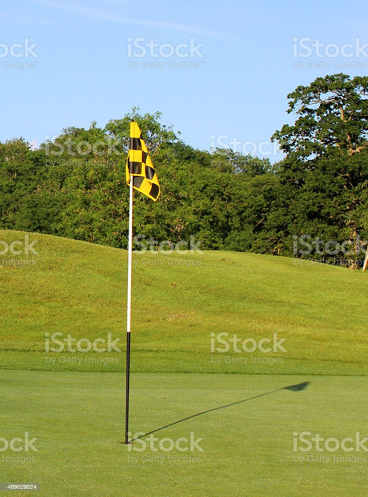Photo showing a golf course on a sunny day, with a neatly mown...