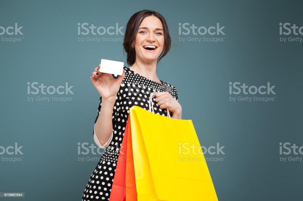 Image of good looking woman in speckled clothes standing with purchases and cutaway in hands royalty-free stock photo