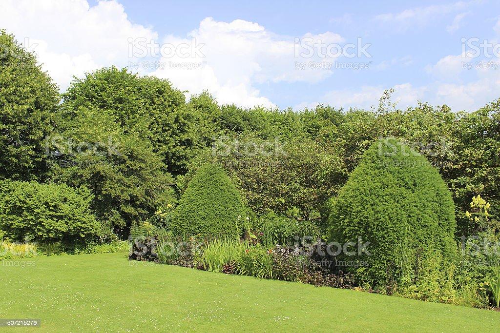 Imagen de jardín verde césped, arbustos autóctonos, herbaceous-flores, sujeción yew árboles, topiaria - foto de stock