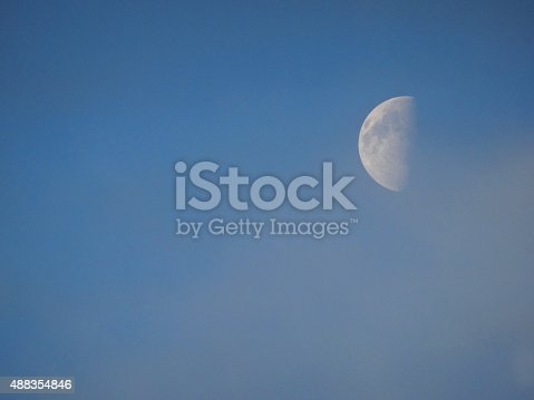 Photo showing a blue sky towards the end of the day, where a half moon is clearly visible.