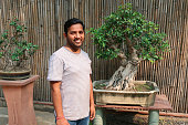 Stock photo of handsome Indian man wearing stripped t-shirt and denim jeans standing in the middle of paved courtyard in garden featuring Japanese elements of bonsai trees on plinths displays