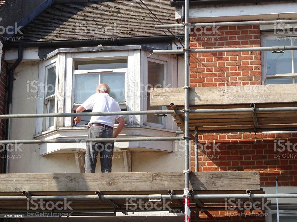 Image of handyman repairing rotten wooden windowframe on scaffolding platform stock photo