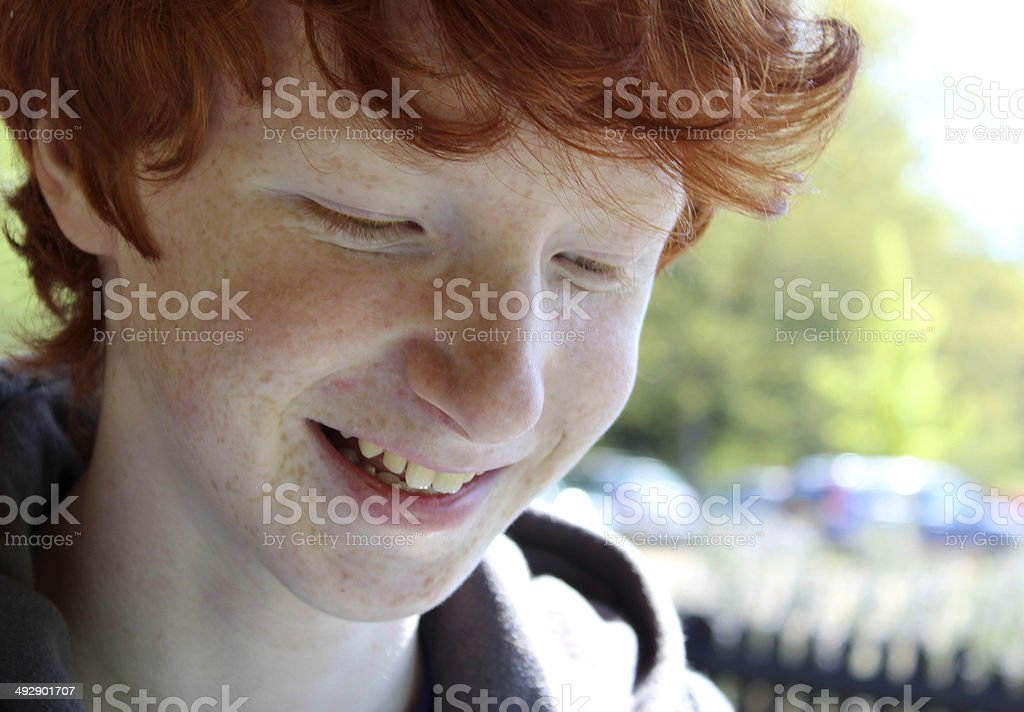 Image of happy boy with red hair smiling to himself stock photo